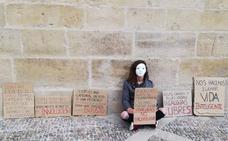 Una mujer protesta junto a la catedral de Santo Domingo contra el encierro del gallo y la gallina