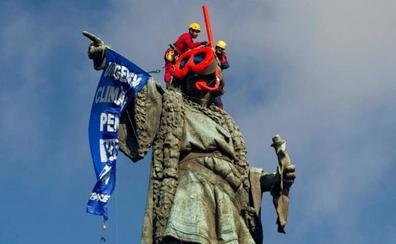 Dos activistas de Greenpeace colocan unas gafas de buzo a la estatua de Colón en Barcelona