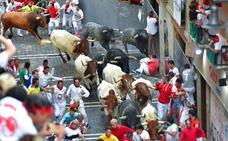 Un toro de Miura cornea a tres corredores en el último encierro de San Fermín